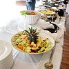 Buffet table with selections of fruit and salad.
