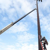 One worker climbs up the pole to attach the crane that is being used to right it, after vandals removed bolts that caused it to lean, on Thursday, January 5. Item Photo / Angela Owens.