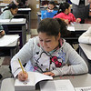 Third grade Hood Elementary School student Keily Rodriguez, front, writes her name in the new dictionary she and every other third grade student in Lynn received today compliments of Lynn Rotary and the Equitable Bank. Photo by Owen O'Rourke