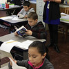Third grade students Karen Fuentes, Jorden LeBlanc, and Christen Gonzalez read the new dictionaries they got from the Equitable Bank and the Lynn Rotary as Hood Elementary School principal Gayle Dufour watches. Photo by Owen O'Rourke