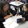 Lauren Pleeter, left, and Awner Mendez, right, a third grade student at the Hood Elementary School in Lynn, look over the new dictionary she received compliments of Equitable Bank and the Lynn Rotary. Photo by Owen O'Rourke