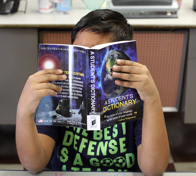 Samin Yasir, a third grade student at the Hood elementary School in Lynn, takes a close look at  the new dictionary he received from the Equitable Bank and the Lynn Rotary. Photo by Owen O'Rourke