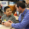 Alan Barrios, left, a third grade student at the Cobbet Elementry School in Lynn, and Tim Burt, right, look up the word noun in the new dictionary Alan just received from the Lynn Rotary Club today. Photo by Owen O'Rourke
