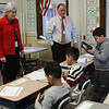Superintendent of Lynn School Dr. Catherine Lahtam, left, and Obie Barker, the Executive Director of the Lynn Boy's and Girl's Club in Lynn, listen to Henry Cruz, a third grade student in the special education class at the Cobbet Elementary School, read the definition of the word Play from the new dictionary he received from the Lynn Rotary Club. Photo by Owen O'Rourke