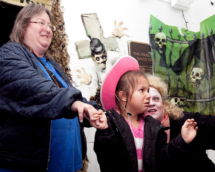 Monica Mendes and her granddaughter Kaylise Mercado, 6, venture through the haunted hallways of Central Scare at Lynn Arts on Thursday, October 25. Item Photo / Angela Owens.