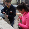 Nicole Greene, left, and Ashley Arezmien, right, trim vinyl siding at 6 Grover Street in Lynn on Saturday. Grover Street was the scene of a Habitat for Humanity project. Photo by Owen O'Rourke