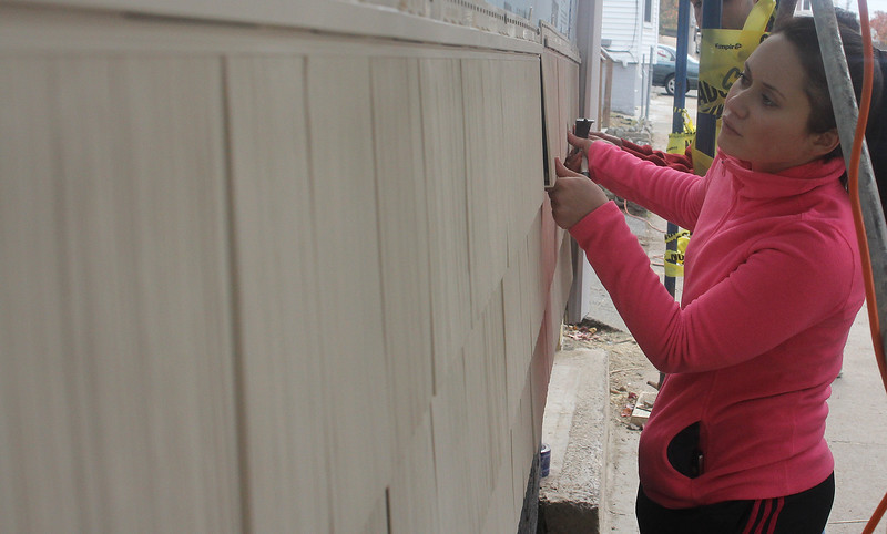 Ashley Arezmien installs siding as part of the Habitat for Humanity project at 6 Grover Street in Lynn on Saturday. Photo by Owen O'Rourke