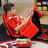 Jaedyn Encarnacao, a second grader at the Oaklandvale Elementary School, using his floor seating and lapdesk combination as part of the flexible seating at the school. Photo by Owen O'Rourke