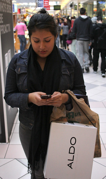 Dayanna Vasquez uses her smart phone to shop at the Square One Mall in Saugus on Black Friday. Photo by Owen O'Rourke
