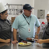 Tony Dunn, middle, who is trying to start a night program for adults at Lynn Technical Vocational Institute, talks with tech students Alondra Hernandez, left, and Johannis De Los Santos, right about food. Photo by Owen O'Rourke