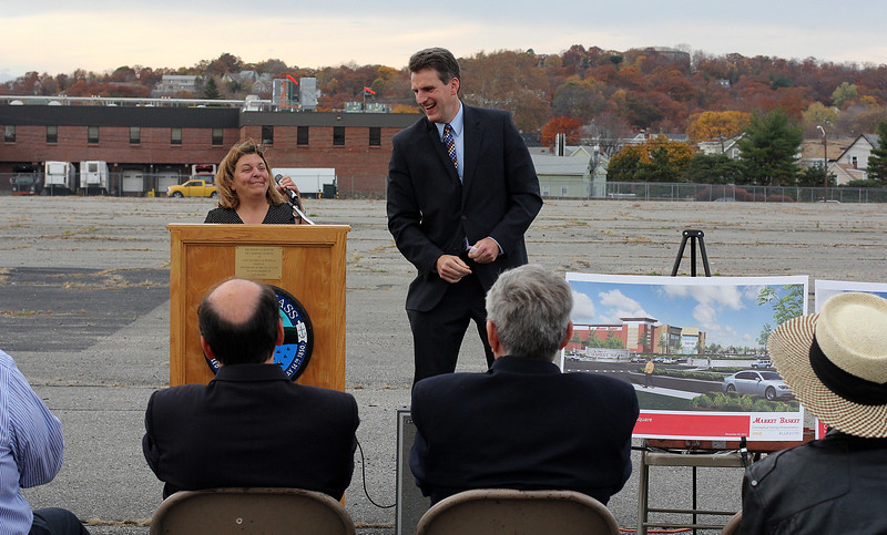 Jay Ash, State Housing and Economic Develoment Secretary, right, hands the podium over to Judith Flangan Kennedy during the ceremony to announce a state grant for infrastructure ceremony at the old General Electric building on Federal Street, site of the new Marketbasket. . Photo by Owen O'Rourke