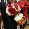 Lorraine DeAmato leads the Veterans Day procession into the gym at St. Mary's High School in Lynn. This is Lorraine's first voyage as a drummer, a role her father Ralph did for years until his death. Behind her is David J. Solimine Sr. this year's keynote speaker and Grace Cotter Reagan, Head of School. Photo by Owen O'Rourke