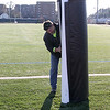 Brian Billingsley putting pads on the goal posts at Manning Field in preperation for Saturday's game. Photo by Owen O'Rourke
