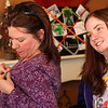 Loree Blanchette, left, of Peabody, pins a green ribbon on herself as her daughter Erica Blanchette, right, greets the host of the Mitochondrial Disease (Mito) social gathering at Christopher's Cafe in Lynn on Saturday. Photo by Owen O'Rourke