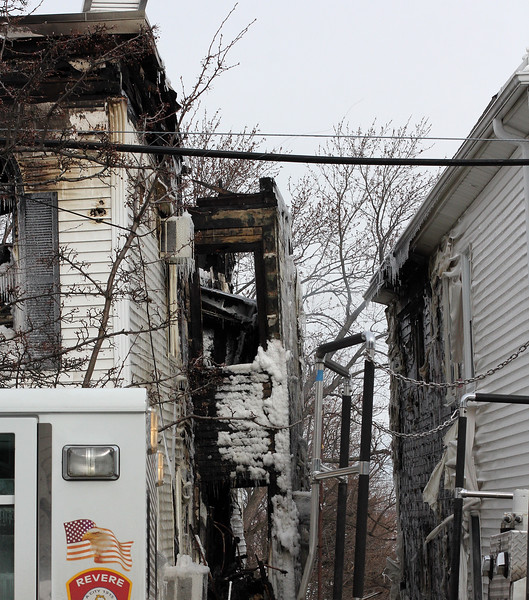 The heat from the 3 alarm fire at 79 Resevoir Ave. in Revere, left, melted the siding on the house next door. Photo by Owen O'Rourke
