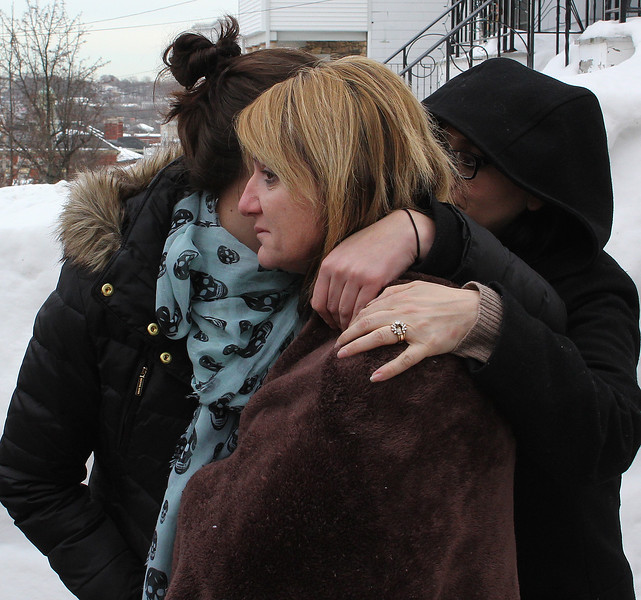 Nextdoor neighbor Felicia Puopolo is comforted by friends. She knew the fire victim, Dennis Toomey, well. He was a great guy. Photo by Owen O'Rourke