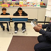 Lynn Police Officer David Woumn reads to students in the sheltered English emersion class at Ingalls Elementary School in Lynn during Community Reading Day on February 7.  From left to right: Patrick Mugisha, Elie Pascasio-Rivera and Better DeLeon.  Photo by Owen O'Rourke