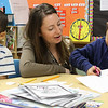 First grade students Edwin Santana, left, and Dawreong Souvannarath, right, work with their teacher Stephanie Franey, middle, on an art project pertaining to the book entitled The Doorbell Rang, by Pat Hutchins that had been read to them during Community Reading Day at the Ingalls Elementary School in Lynn on February 7. Photo by Owen O'Rourke