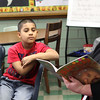 Fourth grade students Medelyn Delgado, left, and Adrian Marquez listen to Dr. Jaye Warry the Deputy Superintendent Lynn Public Schools and one of the guest readers on hand at the Community Reading Day at the Ingalls Elementary School in Lynn on February 7. Photo by Owen O'Rourke