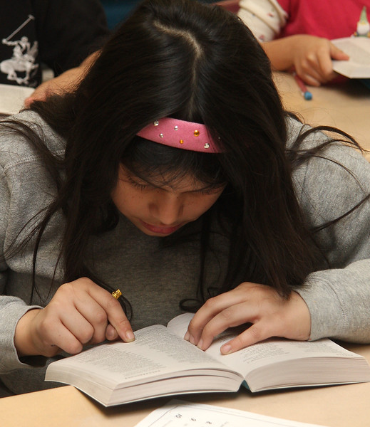 """Kimberly Lopez-Prata, a third grade students at the Connery School in Lynn, looks up the word """"snow"""" in the new dictionary she received from the Lynn Rotary Club today."""