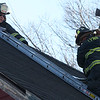 Lynn fire fighters used an abandoned house at 157 Jackson Street in Lynn for training exercises today. Here, Captain Ed Miles, left, supervises fire fighter Jon Godbout as he begins to vent a roof by poking a hole with an ax, after which, a chain saw is brought in to finish the job.