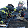 Lynn fire fighters used the abandoned house at 157 Jackson Street for training exercises today. One segment involved venting a roof using an ax followed by a chain saw. Here, Captain Ed Miles, with sunglasses, supervises fire fighter Jon Godbout in venting a roof. The fire fighter has mere minutes to accomplish this task during a fire.