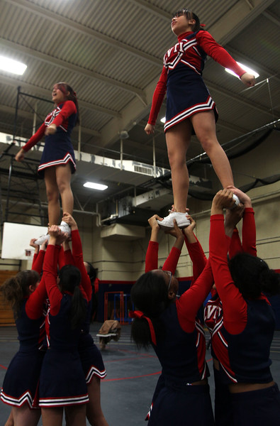 Tech cheerleaders Marina Pheng and Yoselyn Rivera are hoisted above the crowd at their game versus Chelsea  Thursday January 14, 2010. Item Photo/ Reba M. Saldanha