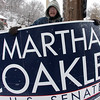 Tom Watkins holding a sign at Briarcliff Lodge in Lynn this morning. His next task was making phone calls.