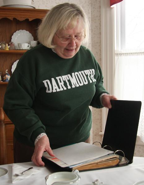 Nancy Perry looking through scrap book.