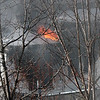 Flames shoot out of the front of the house at 51 Green Street in Lynn just after noon today.