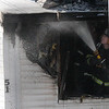 A Lynn fire fighter hosing down one of the front rooms at 51 Green Street in Lynn shortly after noon today.