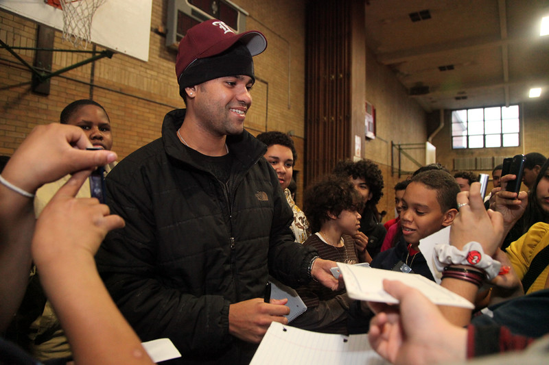 Sporting a hat from Lynn English High school baseball, Red Sox pitcher Manny Delcarmen signs autographs at Marhshall Middle School Monday January 25, 2010. Item Photo/ Reba M. Saldanha