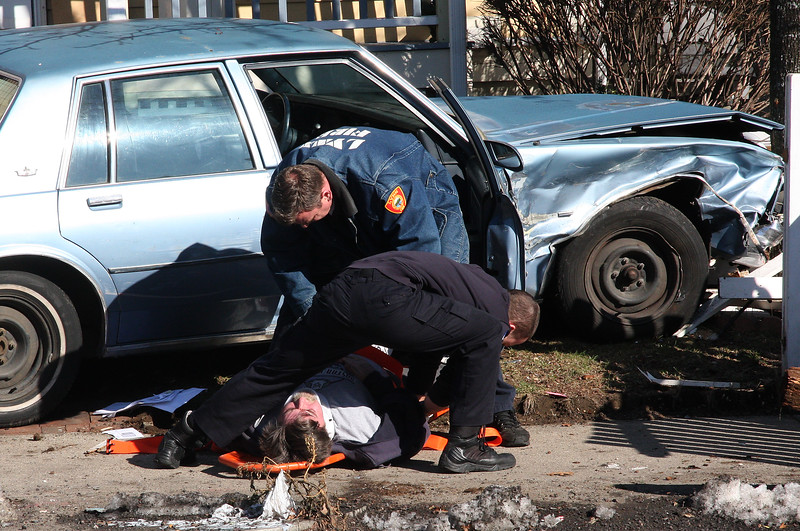 Rescue workers tend to a victim of one of the cars in a two car crash this monring on Washington Street in Lynn.
