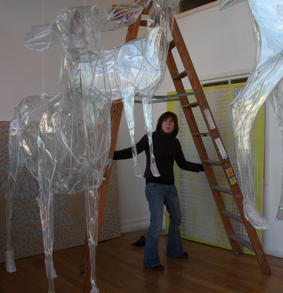 Megan McNaught positions a latter so she can hang her painting at Lynn Arts today. She and artist Christina Pitsch, creator of the reindeer, have a show opening on February 6th and running through March 13.