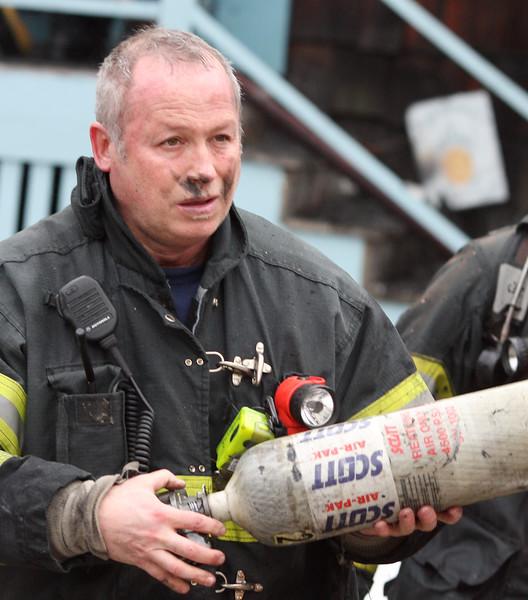 A Lynn firefighter changes oxygen tanks.