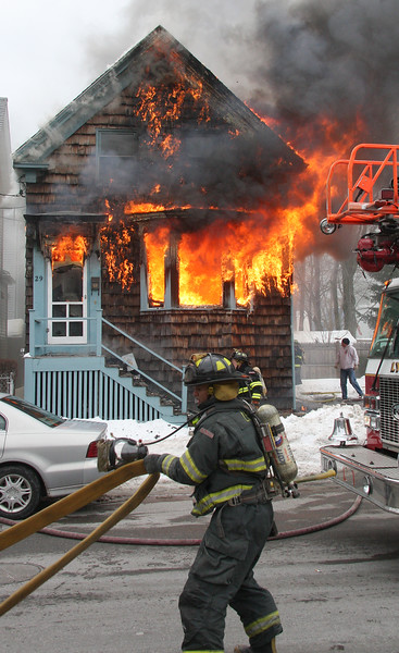 Lynn firefighter lays hose.