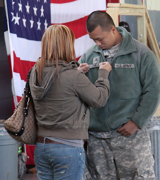 Savoeul Men fixes the name tag on her boyfriend S. Chea from Lynn.