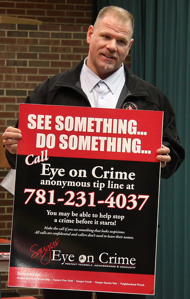 Greg Nickolas, Director of Youth and Recreation in the Town of Saugus,  shows members of the Saugus PTO the new Eye on Crime posters that will soon be on display at every school in Saugus.