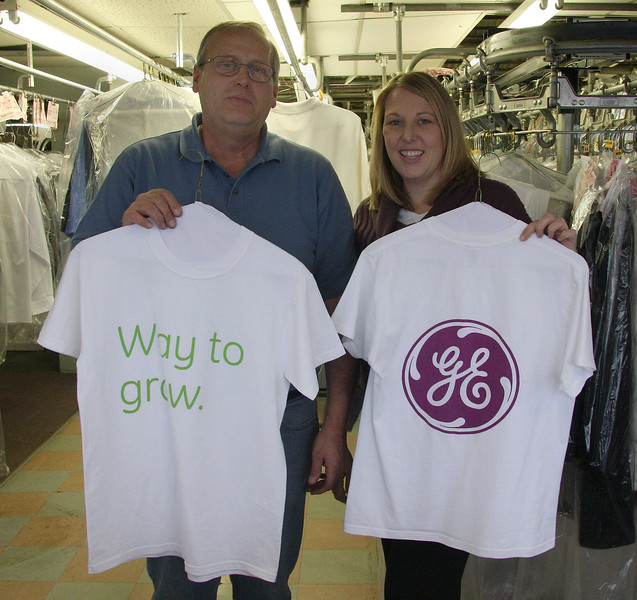 Robert and Ellen Kaminski of Toomey's cleaners in Lynn holding some of the shirts they cleaned for General Electric. The shirts are to shipped to Haiti.