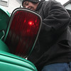Lawrence Nagel, of Rockaway Street in Lynn,  prepares for the coming storm by changing the tail lights in his car.
