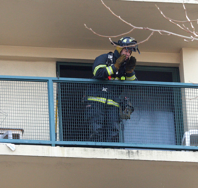A Lynn fire fighter calls down from the balcony on the 8th floor of 95 Tremont Street, scene of a stove fire.