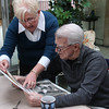 Joan McGovern Regan and Johnny Pesky look at old photos and letters.