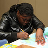 Frances Njinfua works on a school vacation project in the arts and crafts room  at the Lynn Library today.