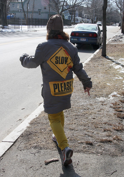 """Katie Reilly of Marblehead goes out for a stroll with name of her organization """"Slow Please"""" on her back. Slow Please was started 20 years ago when Katie went to pick up her daughters and found the body of a young girl from Revere lying on the street, victim of a hit an run driver. The girl lived and the organization began."""