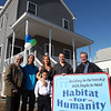 The Morel Family (starting second from left) Jonathan, Onandy, Marilu, and Francisco, poses with Habitat For Humanity North Shore Board Chair Donald Preston, left, and construction supervisor Mark Bergeron, right, outside their new Camden St home in Lynn Sunday February 21. 2010. Item Photo/ Reba M. Saldanha