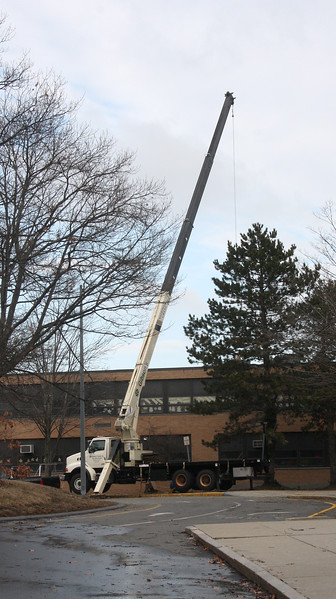 A crane repairing storm damage to the roof of the Swampscott Middle School.