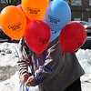 Eddie DeSisto ties balloons to the sign announcing the 2010 census outside of the Lynn Community  Health Center today.