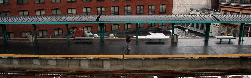 Tell me how long the trains been gone. A lone commuter waits for the train in Lynn.