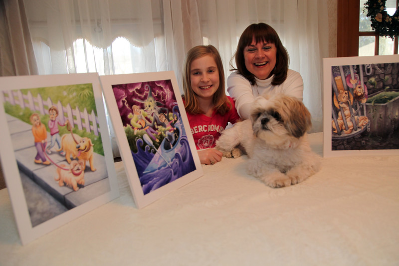 The Witches That Saved the Dogs co-authors and Peabody residents Lily Ditchfield, left, and Julie Zielski pose with Shih Tzu Emma and the original illustrations in the Zielski home Tuesday March 9, 2010. Item Photo/ Reba M. Saldanha