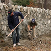 Larry Cabrell and Robert Tshea clean up after rebuilding a 36 foot section of stone wall in the Riverside Cemetery in Saugus.